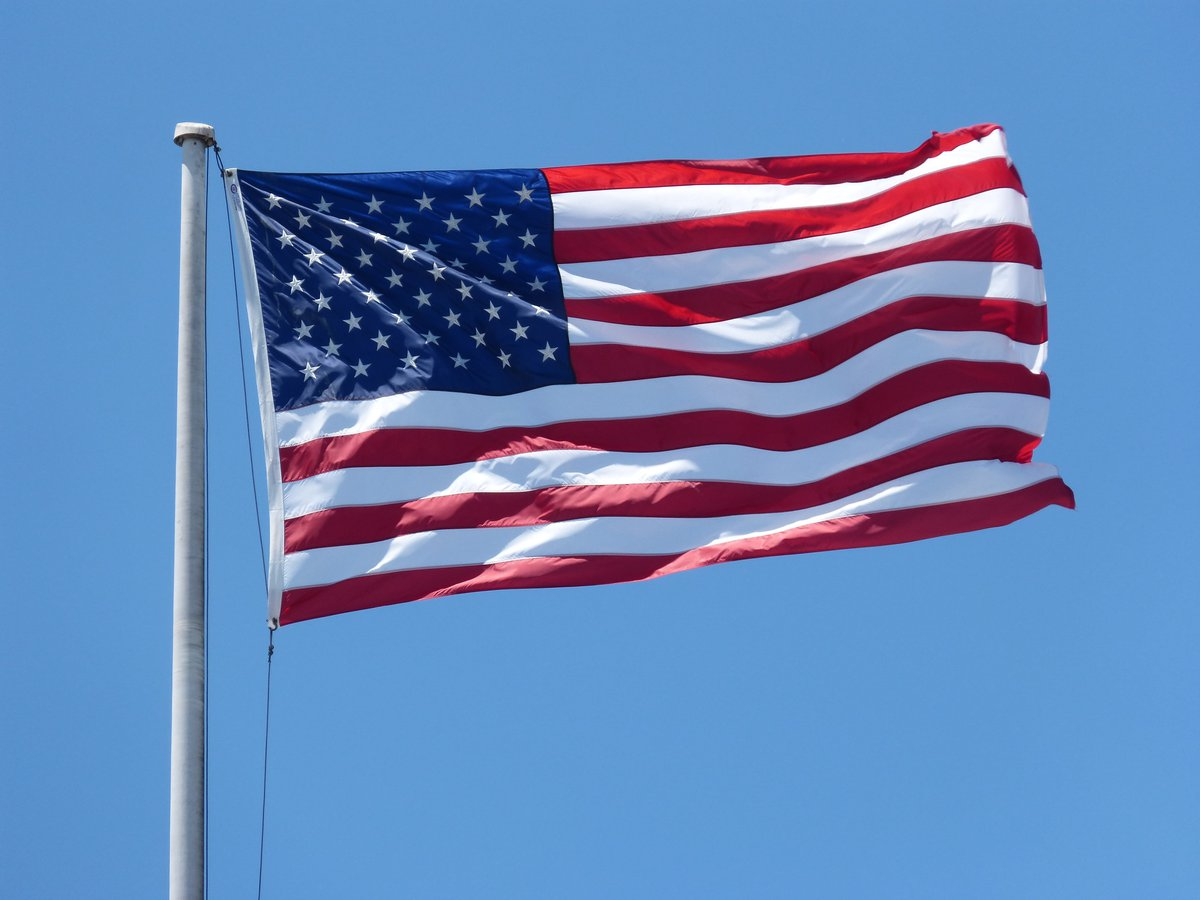 Photo of American flag waving against blue sky